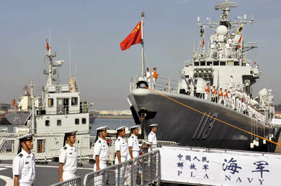 Chinese navy sailors stand on the guided-missile destroyer, Qingdao, before departure for a naval drill at a military port in Qingdao in east China. (Photo: AAP)