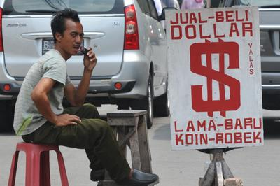 An Indonesian man waits for customers at a street money changer in Jakarta on August 28, 2013.  (Photo: AAP)