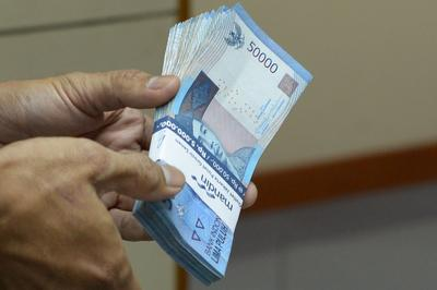 This picture taken in Jakarta on August 28, 2013 shows an Indonesian clerk handling a stack of Indonesian rupiah notes at a money changer office in Jakarta. (Photo: AAP)