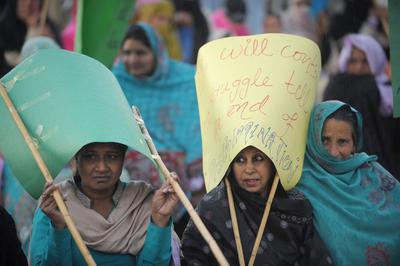 Pakistani human rights activists hold placards at a rally to mark International Women (Photo: AAP)