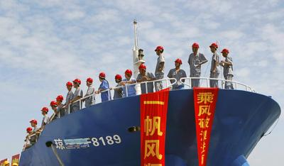 Chinese staff stand on a fishing vessel setting sail for the Spratly Islands, an archipelago disputed between China and other countries including Vietnam and the Philippines. (Photo: AAP)