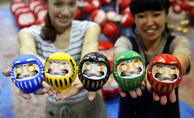 In this 12 September 2013 photo, Daruma dolls, a symbol of good luck, in Olympic colors are shown at a workshop in Takasaki, Gunma prefecture. Tokyo will host the 2020 Summer Olympics and Paralympics. (Photo: AAP)