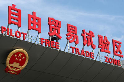 A Chinese worker installs signs of the China (Shanghai) Pilot Free Trade Zone on a gate of the Shanghai Waigaoqiao Free Trade Zone, part of the pilot zone, in Pudong, Shanghai, China, 26 September 2013. (Photo: AAP)