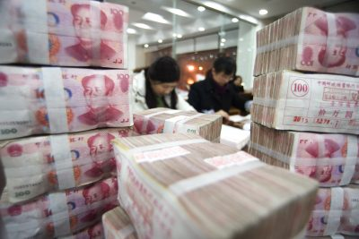 Chinese clerks count RMB (renminbi) yuan banknotes at a bank in Haian county, in Eastern China, on 5 February 2013 (Photo: AAP).