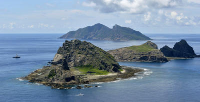 In this Sept. 2, 2012 photo, the survey ship Koyo Maru, left, chartered by Tokyo city officials, sails around Minamikojima, foreground, Kitakojima, middle right, and Uotsuri, background, the tiny islands in the East China Sea, called Senkaku in Japanese and Diaoyu in Chinese. (Photo: AAP)