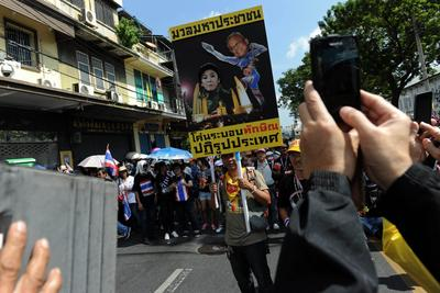 A Thai opposition protester holds up a placard showing protest leader Suthep Thaugsuban hitting prime minister Yingluck Shinawatra during a rally at the Interior Ministry in Bangkok on 1 December 2013. (Photo: AAP)