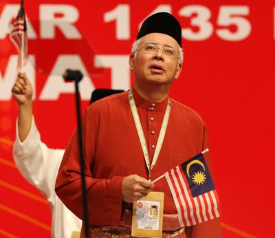 Malaysian Prime Minister Najib Abdul Razak holds the national flag during the opening ceremony of the UMNO 67th General Assembly in Kuala Lumpur, 5 December 2013. (Photo: AAP)