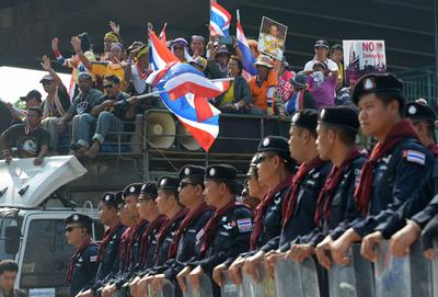 Thai anti government protesters wave national flags next to riot police during a demonstration at Army Club in Bangkok on 10 December 2013. (Photo: AAP)