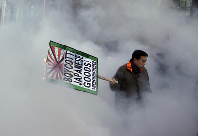 A South Korean protester burns an anti-Japan banner after police officers spray fire extinguisher during a rally against Japanese Prime Minister Abe in front of the Japanese Embassy in Seoul on Friday, 27 December 2013, following the Yasukuni Shrine visit. (Photo: AAP)