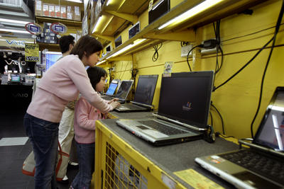 A mother and daughter try a new laptop at a major electronics market in Taipei, Taiwan. (Photo: AAP)