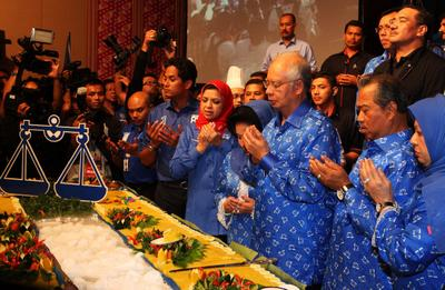 Malaysian Prime Minister Najib Abdul Razak prays with senior party members during a celebration after winning the 13th general elections 6 May 2013. (Photo: AAP).