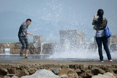 A man reacts as a wave hits a sea wall at a beach on Pingtan island, Fujian province. Located off the east coast of China's Fujian province, Pingtan island is the country's 5th largest and relies heavily on a tourism-driven economy, although an 'experimental zone' aims to draw in foreign investment from neighboring Taiwan. (Photo: AAP)