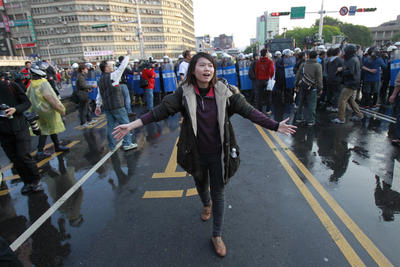 A student protesting against a China Taiwan trade pact begs for fellow protesters not to intimidate riot police clearing the streets around the government Cabinet buildings in Taipei, Taiwan, 24 March 2014. (Photo: AAP)