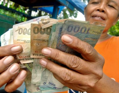 A stallholder counts out her rupiah at the end of the business day in Jakarta, 16 May 2006. (Photo: AAP)