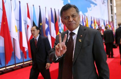 Former ASEAN Secretary General Surin Pitsuwan makes a victory sign as he walks into the plenary session on global issues at the ninth Asia Europe Summit at the National Convention Centre in Vientiane, Laos, 6 November 2012. (Photo: AAP)