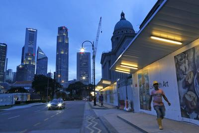 A foreign construction worker from Bangladesh walks past the city hall construction site with the Singapore skyline in the background in Singapore. (Photo: AAP)