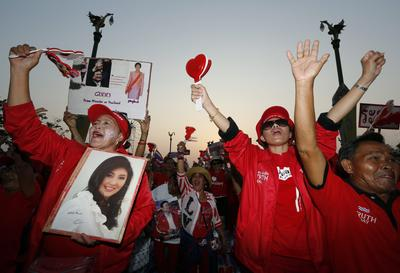 A Thai pro-government Red Shirt protester holds a placard showing a picture of caretaker Thai Premier Yingluck Shinawatra during a rally on the outskirts of Bangkok, Thailand, 6 April 2014. (Photo: AAP)