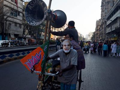 A rickshaw puller, wearing a mask of Bharatiya Janata Party prime ministerial candidate and Gujarat state Chief Minister Narendra Modi, transports loudspeakers during a rally in Kolkata on 1 February 2014. Modi, tipped in opinion polls to be India