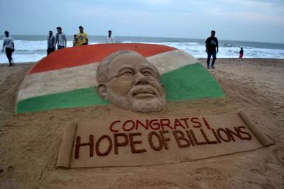 Indians walk past a sand sculpture of new prime minister Narendra Modi created by sand artist Sudarsan Pattnaik at Puri beach, some 65 kilometers from Bhubaneswar on 27 May 2014. (Photo: AAP)
