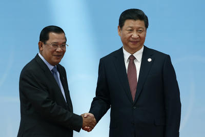 Cambodian prime minister Hun Sen, left, and Chinese president Xi Jinping shake hands while at a multinational conference in Shanghai on Wednesday 21 May 2014. Both the Philippines and Vietnam have blamed Cambodia for blocking discussions on Chinese aggression in the South China Sea at the 2012 ASEAN summit. (Photo: AAP)
