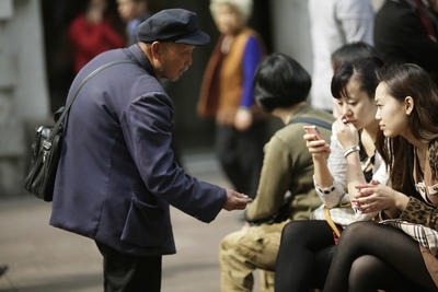 A beggar asks for money from people sitting at a pedestrian mall in Shanghai, China, 19 April 2012. (Photo: AAP)