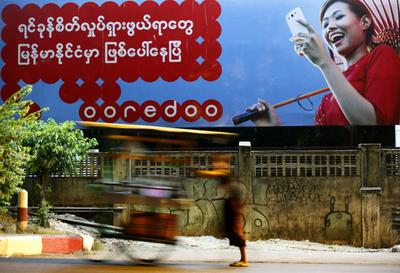 A Myanmar man pushes his cart past a billboard displaying advertising for Ooredoo, a telecommunications provider with headquarters in Qatar that recently won a license to develop the Myanmar network, in Yangon, Myanmar, 5 April 2014. (Photo: AAP)