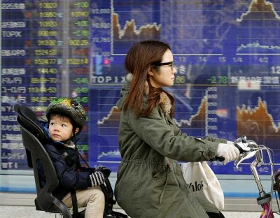 A mother and child cycle past an electronic stock board of a securities firm in Tokyo, 21 January 2013. With the aim of increasing the female labour force participation rate, the Japanese government has begun to allocate significant resources to tackling longstanding childcare shortages. (Photo: AAP)