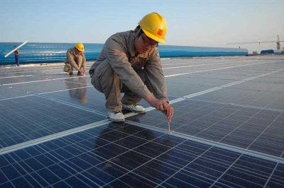 Chinese workers install solar panels on the rooftop of a workshop at a textile factory of Guanxing Group in Liaocheng city, Shandong province, China, 30 October 2012. China has become the world's largest producer of solar panels and wind turbines. (Photo: AAP)