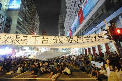 Pro-democracy protesters continue a sit-in demonstration under a banner calling for the resignation of Chief Executive CY Leung and genuine elections in downtown Hong Kong, 6 October 2014. The protests are about economics as much as democracy, argues Peter Cai. (Photo: AAP)