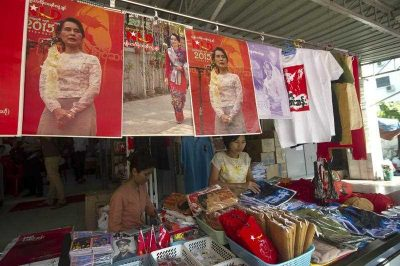 Members of the National League for Democracy (NLD) work at a souvenir stall beneath posters of Myanmar's opposition leader Aung San Suu Kyi at the party headquarters in Yangon on 19 November 2014. (Photo: AAP).