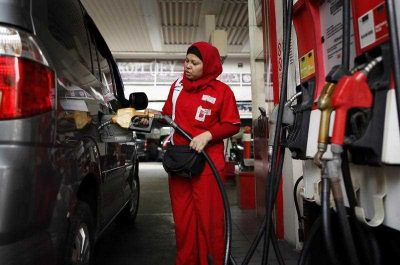 An Indonesian employee fills a car with subsidised fuel at a petrol station in Jakarta, Indonesia, 24 November 2014. Incoming President Joko Widodo has lowered fuel subsidies but, like Susilo Bambang Yudhoyono, has not removed them altogether or linked to global prices. (Photo: AAP).