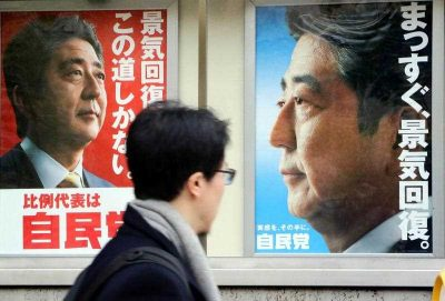 A man walks past posters of Japanese prime minister and ruling Liberal Democratic Party (LDP) leader Shinzo Abe displayed at the LDP headquarters in Tokyo on 4 December 2014. (Photo: AAP).
