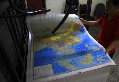 A printing worker holds a new officially approved map of China that includes the islands and maritime area that Beijing claims in the South China Sea, at a factory in south China's Hunan province on 27 June 2014. (Photo: AAP).