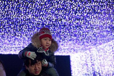 A man carries a child on his shoulders as they visit an annual lights festival held at a shopping mall in Beijing, 27 December 2014. The month long festival spans Christmas and New Year, giving retailers a chance to boost sales as they ring in the New Year. (Photo: AAP).