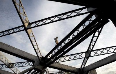 A boy walks on one of the trusses of the Quezon Bridge in Manila. (Photo: AAP).