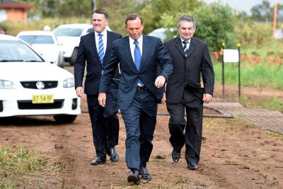 Prime Minister Tony Abbott, is greeted by Assistant Minister for Infrastructure and Regional Development, Jamie Briggs, and Federal member for Macarthur Russell Matheson, as he arrives to announce the start of the upgrade to Bringelly road, in Sydney, 20 January 2015. The Australian government's focus on putting its budget on a 'credible path back to surplus' over the medium term, appears to rule out any substantial infrastructure investment program as a form of stimulus. (Photo: AAP).