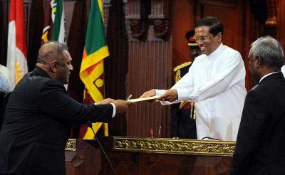 New Sri Lankan President Maithripala Sirisena hands a letter of appointment to Mangala Samaraweera as the Minister of Foreign Affairs during the swearing-in of the new Cabinet in Colombo, 12 January 2015. (Photo: AAP).