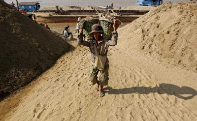 Myanmar worker carries two baskets loaded with gravel on his shoulders as he unloads a boat to a jetty of Yangon River, Yangon, Myanmar, 27 January 2015. (Photo:AAP).