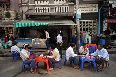 Customers sitting with drinks at a traditional roadside coffee shop in downtown Yangon, Myanmar, 28 January 2015. (Photo: AAP).