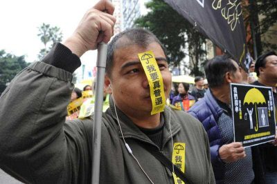 "A pro-democracy protester, putting a yellow sticker reading "" I want real universal suffrage in Hong Kong on Feb. 1, 2015. Thousands of demonstrators took the street for the first time since last year and held up yellow umbrellas, a symbolo of the Occupy Central momvement during a march through central Hong Kong. (Photo: AAP)"