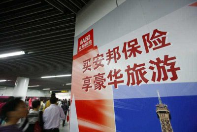 Passengers walk past an advertisement for Anbang Insurance at a metro station in Shanghai, China, 18 October 2012. Anbang Insurance Group Co, a little-known Chinese insurer until last year, has gained sudden prominence in the financial and capital markets after a string of high-profile domestic and international acquisitions. The company has been rapidly building a financial empire over the past few years by purchasing stakes of the country's banks, insurers and real estate developers, while extending its reach to financial leasing, asset management and securities brokerages through the operation of its 10 subsidiaries. (Photo: AAP)