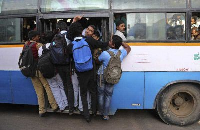 Indian students travel in a crowded bus during the morning rush hour in Bangalore, India. (Photo: AAP).