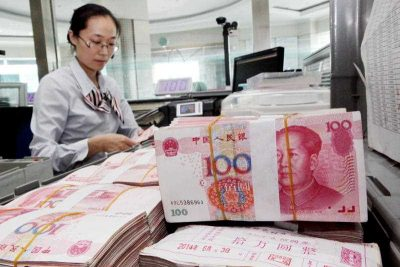 A Chinese clerk counts RMB (renminbi) banknotes. (Photo: AAP).