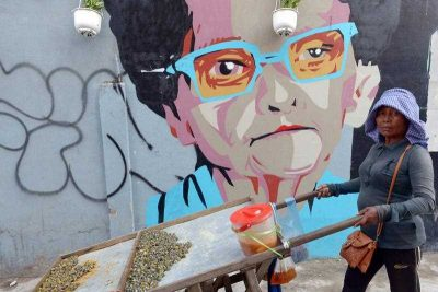 A vendor pushes her cart containing river shell fish past a graffiti artwork upon a wall in Phnom Penh. (Photo: AAP).