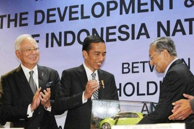 Former Malaysian Prime Minister Mahathir Mohamad presents a souvenir to visiting Indonesian President Joko Widodo as Malaysia's Prime Minister Najib Razak looks on at the head office of automaker Proton Holdings Bhd. in Shah Alam outside Kuala Lumpur on 6 February 2015. (Photo: AAP)