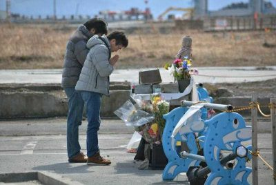 People pray for the victims of 3/11 earthquake and tsunami at the former disaster control centre in Minamisanriku, Miyagi prefecture, Japan on 9 March 2014. (Photo: AAP).