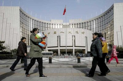 Pedestrians walk past the head office of the People's Bank of China (PBoC), China's central bank, in Beijing. (Photo: AAP).