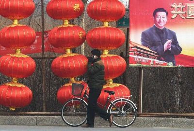 A man walks past a billboard featuring a photo of Chinese President Xi Jinping beside lantern decorations for the Lunar New Year in Baoding, China's northern Hebei province on 24 February 2015. (Photo: AAP).