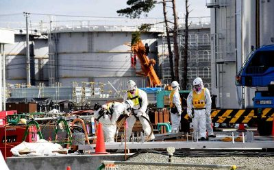 Workers wearing protective suits construct tanks to store contaminated water at the Fukushima No. 1 nuclear power plant. Sensors of the Tokyo Electric Power Company (TEPCO) have detected a new leak of highly radioactive water, 23 February 2015. The firm has continued to decommission the crippled plant. (Photo: AAP).