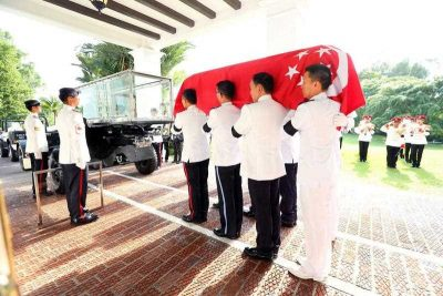 Officers lift the coffin of late Lee Kuan Yew prior to his procession to Parliament House, at Istana Palace, Singapore, 25 March 2015. (Photo: AAP)